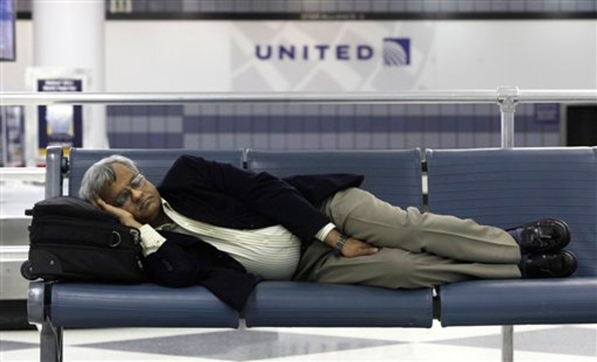 A stranded United Airlines passenger sleeps in Terminal 1 at O'Hare International Airport Saturday, June 18, 2011 in Chicago. Thousands of flyers were stranded Friday night in airports across the country when United Airlines computers crashed, interrupting departures and reservations and disrupting the airline's websites.  (AP Photo/Charles Rex Arbogast)      (AP)