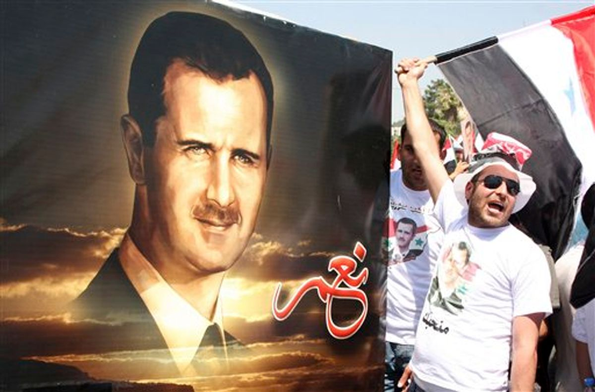 """A Syrian shouts pro-Syrian President Bashar Assad slogans, as others carry a picture of Assad with writing in Arabic that reads:"""" Yes,"""" during a rally in support of Assad, in Damascus, Syria, Tuesday, June 21, 2011. Tens of thousands of people waving flags and pictures of Assad converged on Syria's main squares Tuesday, pledging allegiance to their president in the latest show of government support to counter a three-month uprising against his authoritarian rule. (AP Photo/Bassem Tellawi) (AP)"""
