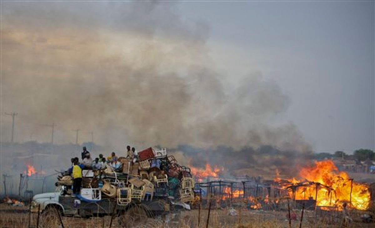 In this photo provided by the United Nations Mission in Sudan (UNMIS), a truck piled high with looted items drives past the burning huts of businesses and homesteads in the center of Abyei town, Sudan Saturday, May 28, 2011. Tens of thousands of Sudanese are fleeing from the contested north-south border region of Abyei, and the top U.S. official in the region warned Friday of a humanitarian crisis over the north's invasion. (AP Photo/UNMIS, Stuart Price) EDITORIAL USE ONLY, NO SALES  (AP)