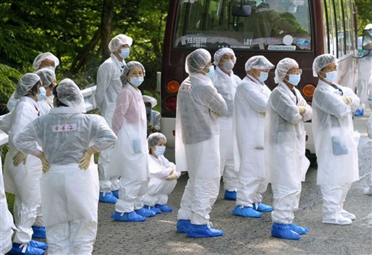 Evacuees in protective clothing wait for a substitute bus to come beside their disabled bus, after they returned for a a brief visit to their houses in the exclusion area, in Okuma, Fukushima prefecture, northeastern Japan, Saturday, June 4, 2011. The tsunami-crippled Fukushima Dai-ichi nuclear power plant is located in the town. (AP Photo/Kyodo News) JAPAN OUT, MANDATORY CREDIT, NO LICENSING IN CHINA, HONG KONG, JAPAN, SOUTH KOREA AND FRANCE (AP)