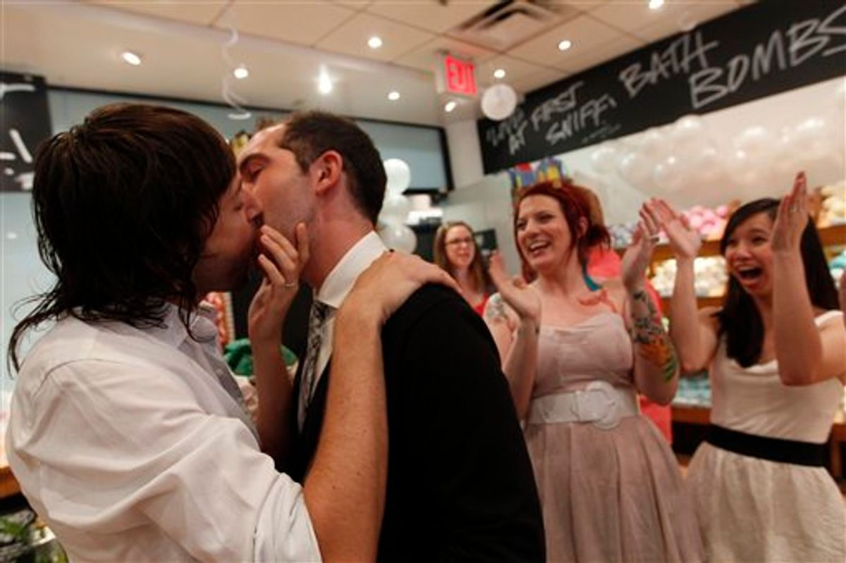 Lush Cosmetic employees Daniel Gervais, left, and David Casavant take part in a Kiss and Tell event in support of marriage equality as Amanda Halderman, second from right, and Perry Sun cheer them on, Saturday, June 18, 2011 in New York.  The State Senate left the Capitol on Friday without tackling same-sex marriage and other key issues, but Gov. Andrew M. Cuomo insisted lawmakers are on track to take action before the end of the legislative session slated for Monday. (AP Photo/Mary Altaffer) (AP)