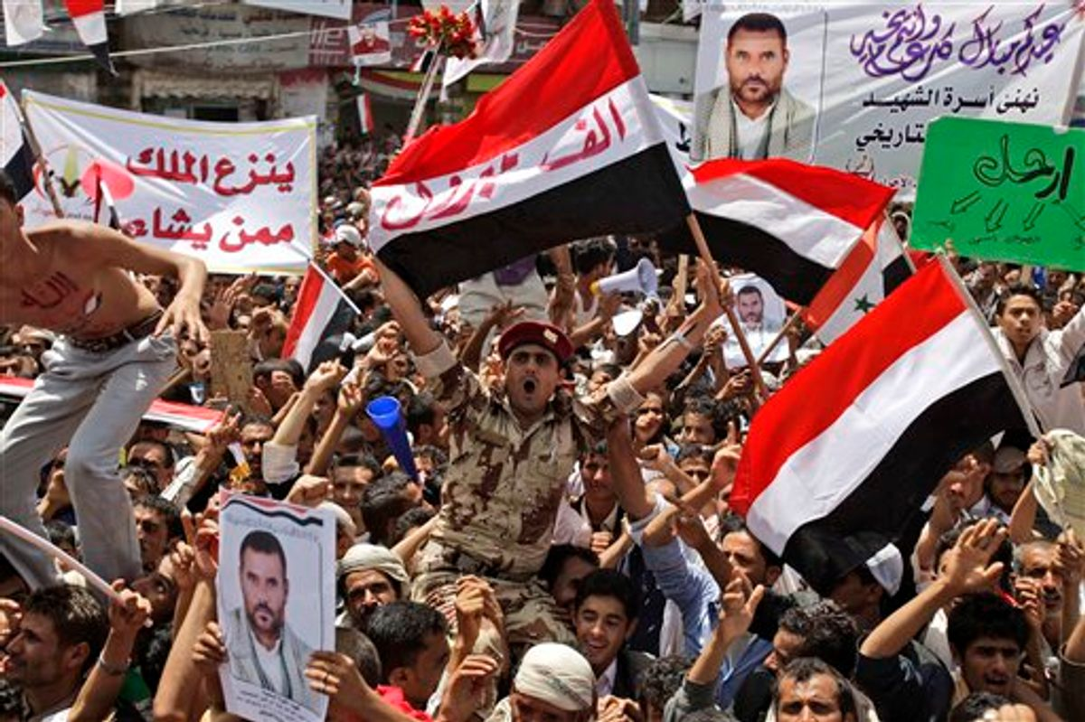 """A Yemeni army soldier, center, lifted by anti-government protestors, reacts holding up his national flag with Arabic reads on it, """" A thousand congratulations"""", as he and other demonstrators celebrate President Ali Abdullah Saleh's departure to Saudi Arabia, in Sanaa, Yemen, Sunday, June 5, 2011. Thousands of protesters are dancing and singing in the Yemeni capital Sanaa after the country's authoritarian leader flew to Saudi Arabia to receive medical treatment for wounds he suffered in a rocket attack on his compound. (AP Photo/Hani Mohammed) (AP)"""