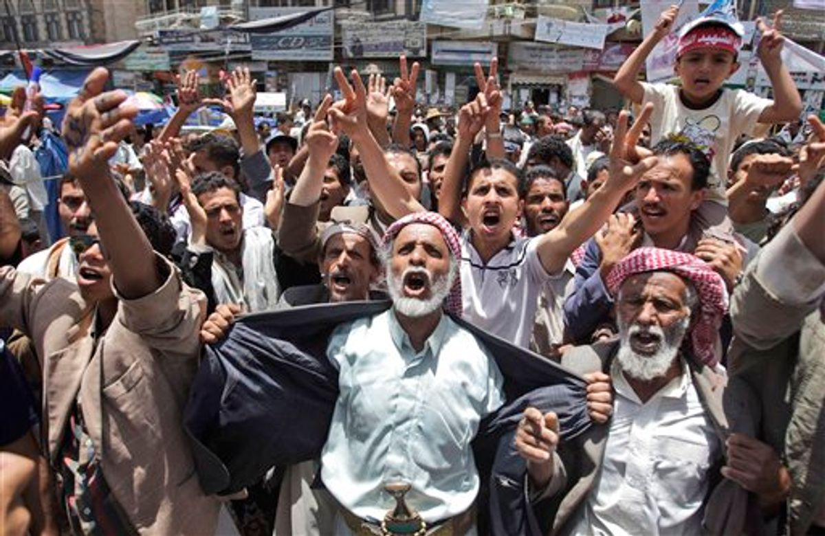 Anti-government protestors react during a demonstration demanding the resignation of Yemeni President Ali Abdullah Saleh, in Sanaa, Yemen, Monday, May 30, 2011. Yemeni warplanes carried out airstrikes Monday on a southern town seized by hundreds of Islamic militants over the weekend, witnesses said, as the political crisis surrounding the embattled president descended into more bloodshed. (AP Photo/Hani Mohammed) (AP)