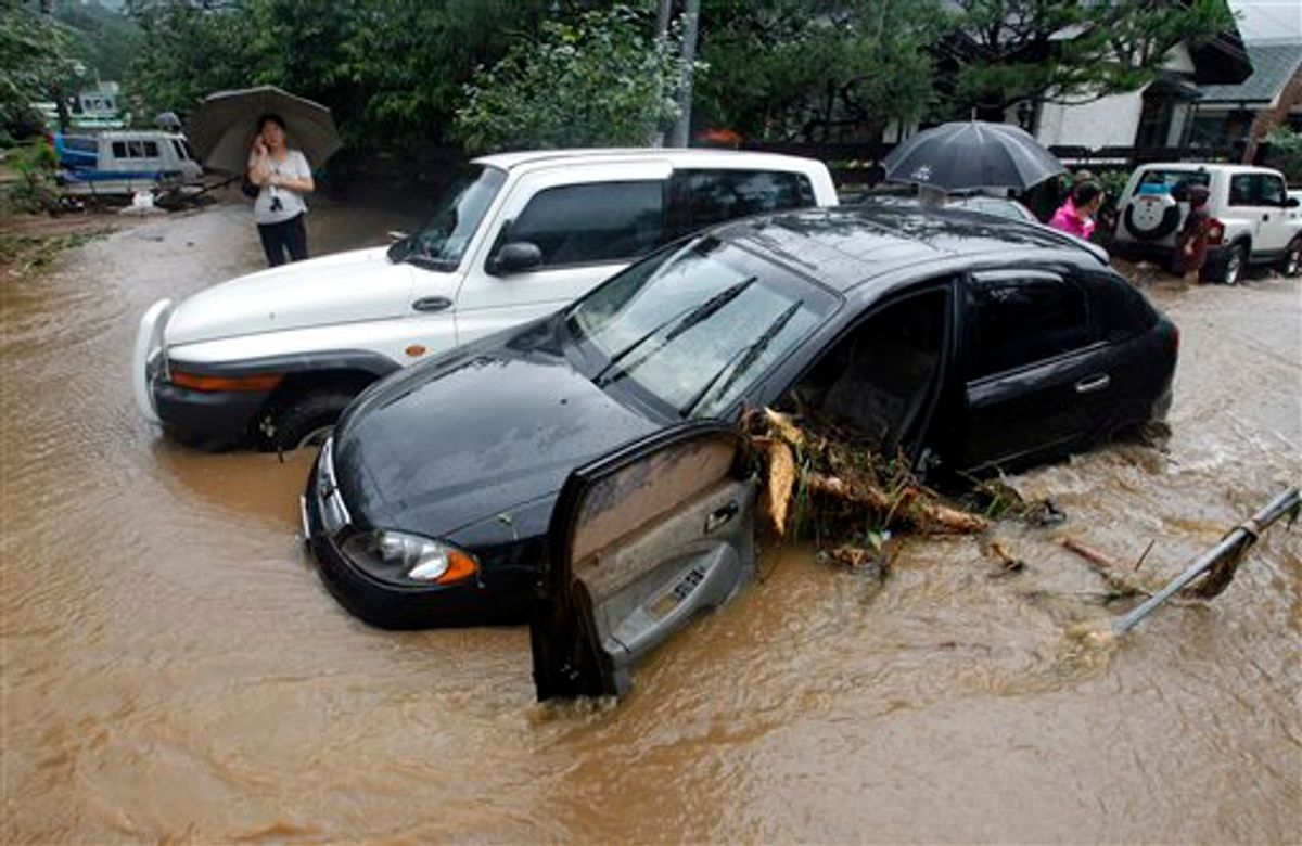 A resident uses her mobile phone near wrecked vehicles after a landslide caused by heavy rains in in Seoul, South Korea, Wednesday, July 27, 2011. A quick blast of heavy rain sent landslides barreling through South Korea's capital and a northern town Wednesday. (AP Photo/ Lee Jin-man) (AP)