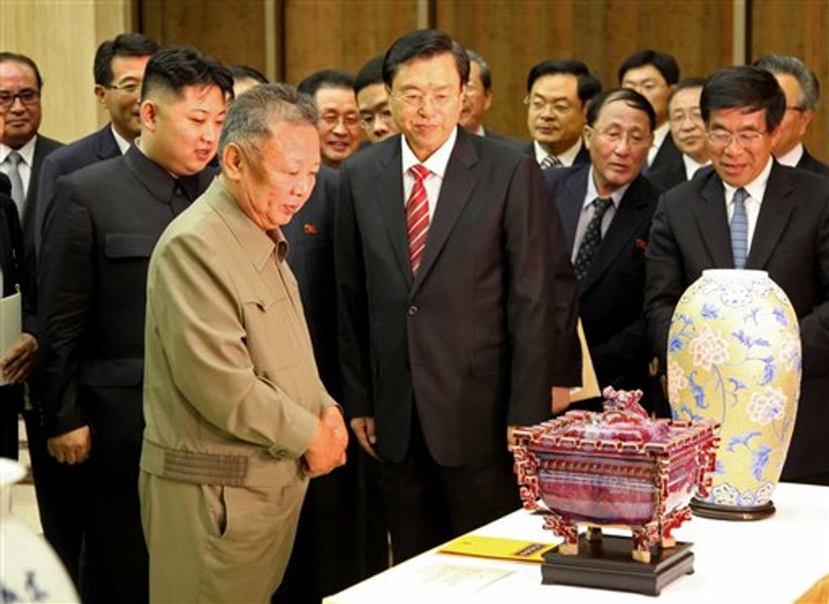 In this photo released by China's Xinhua News Agency, North Korean leader Kim Jong Il, front left, looks at gifts presented to him by Chinese Vice Premier Zhang Dejiang, center, head of a Chinese delegation to celebrate the 50th anniversary of the Treaty of Friendship, Cooperation and Mutual Assistance Between China and Democratic People's Republic of Korea, in Pyongyang, North Korea, on Tuesday, July 12, 2011. Kim Jong Il's son Kim Jong Un stands behind his father. (AP Photo/Xinhua, Zhang Li) NO SALES                      (AP)