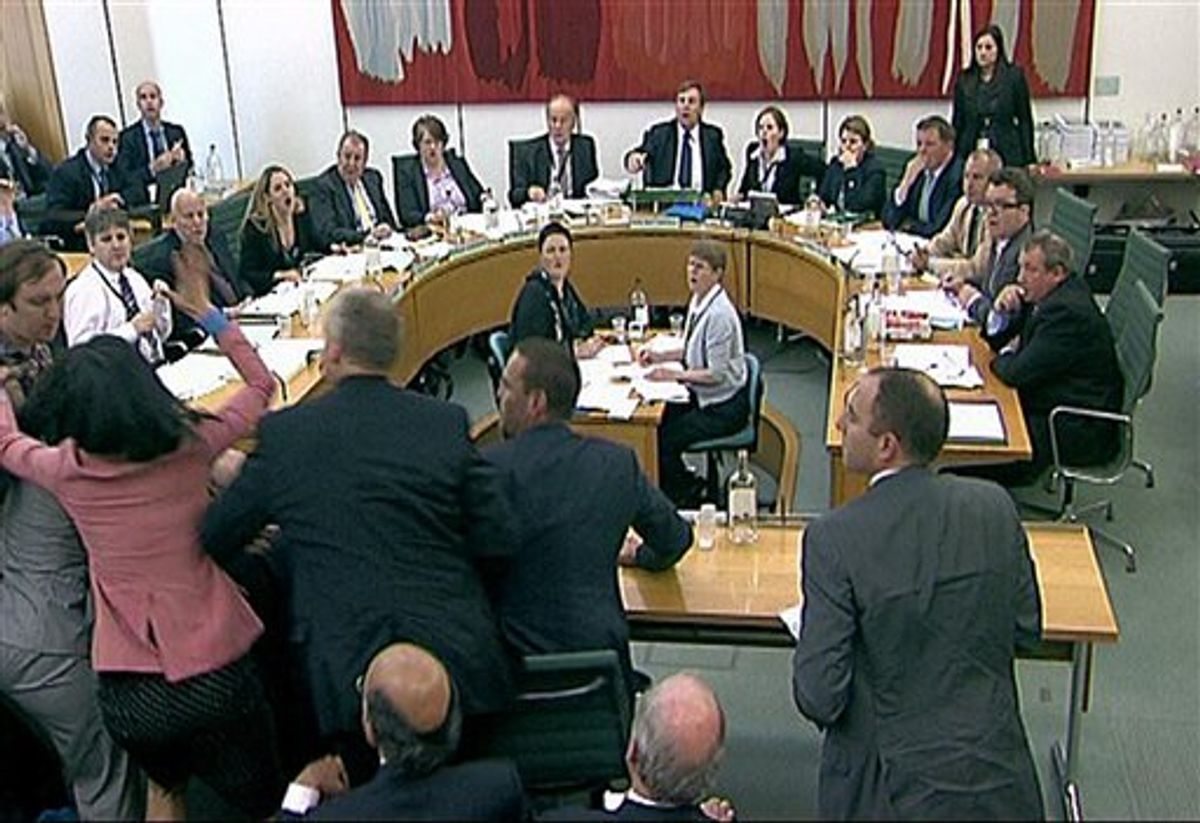Committee members react after a protestor, left checked shirt , named on Twitter as Jonnie Marbles, tries to throw  a paper plate covered in shaving foam over Rupert Murdoch as he gave evidence to a House of Commons Committee in London, Tuesday July 19, 2011, on the News of the World phone hacking scandal.(AP Photo/pa)  UNITED KINGDOM OUT: NO SALES: NO ARCHIVE: (AP)