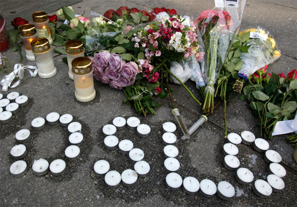 Candles and flowers are arranged on the ground near the blast site to mourn victims of the attacks