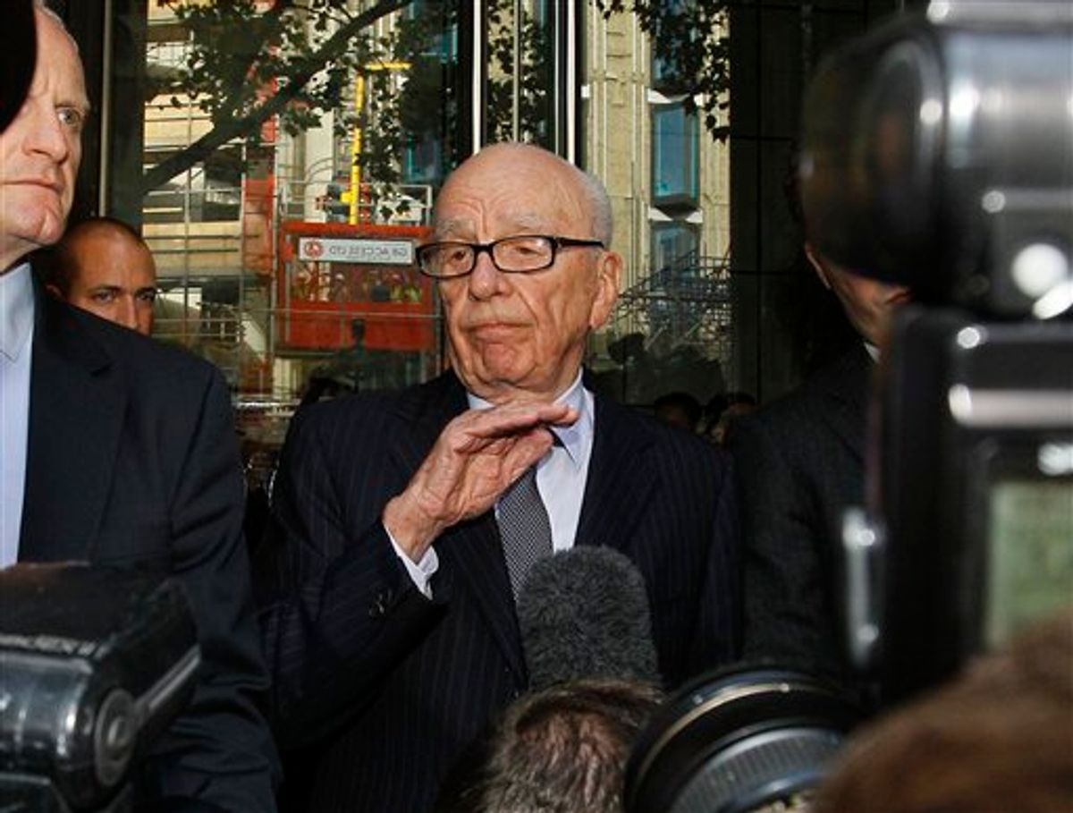 """Rupert Murdoch, centre, attempts to speak to the media after he held a meeting with the parents and sister of murdered school girl Milly Dowler in London, Friday, July 15, 2011. The lawyer for the Milly Dowler's family says Rupert Murdoch has issued a full and sincere apology to the murdered schoolgirl's family for the actions of journalists at his newspaper. Mark Lewis told reporters that the media baron called the private meeting and apologized """"many times,"""" telling the Dowlers the events that transpired at the News of the World tabloid were not in keeping with the standards set out when his own father entered the media industry.(AP Photo/Kirsty Wigglesworth)      (AP)"""