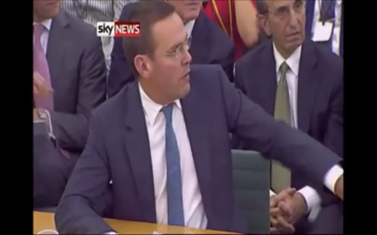 James Murdoch reacts with shock as an activist lunges towards his father Rupert with a cream pie