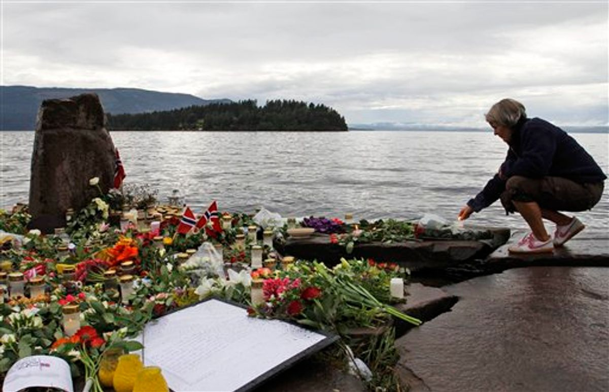 A woman lights a candle in Sundvollen, facing Utoya island, where gunman Anders Behring Breivik killed at least 68 people, near Oslo, Norway, Tuesday, July 26, 2011. Norwegian police on Tuesday began releasing the names of those killed in last week's bomb blast and massacre at a youth camp, an announcement likely to bring new collective grief to an already reeling nation. (AP Photo/Ferdinand Ostrop) (AP)