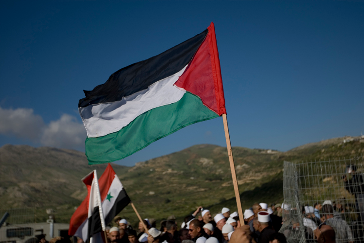 Druze men wave Palestinians and Syrian flags as they stand near the border fence between Israel and Syria on May 15, 2011
