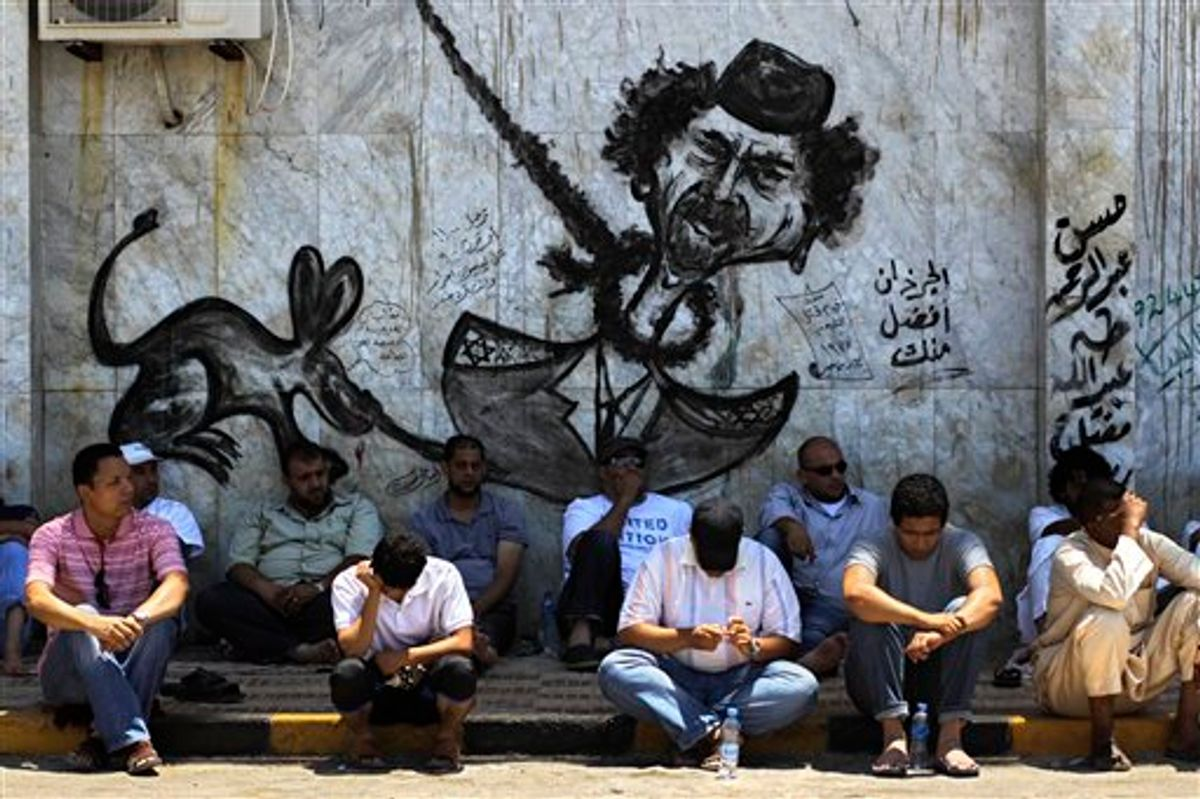 LIbyans sit in the shade under a graffiti depicting Libyan dictator Moammar Gadhafi before a Friday prayer in rebel-held Benghazi, Libya, Friday, July 8, 2011. NATO denied a Libyan government charge Thursday that the alliance is intentionally using its airstrikes to assist rebel advances, saying it is sticking to its mandate to protect civilians. (AP Photo/Sergey Ponomarev) (AP)