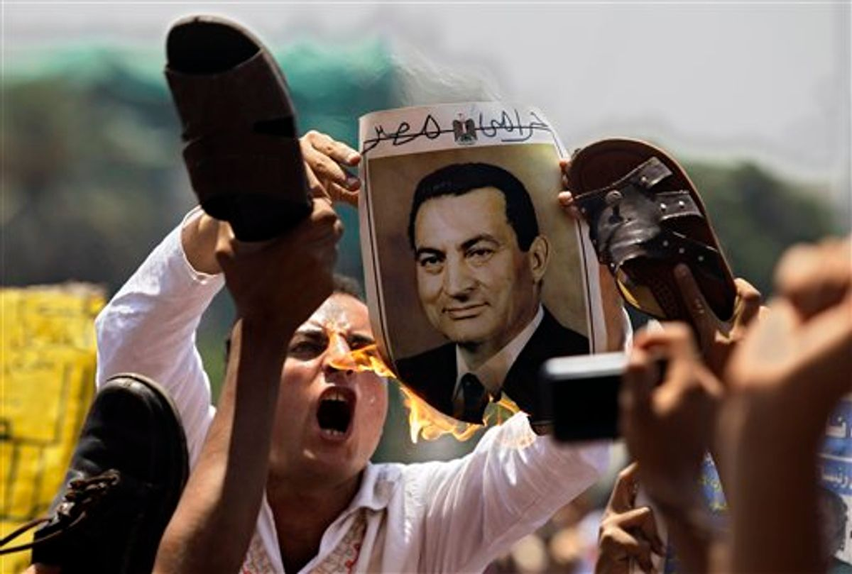 A man burns a picture of ousted Egyptian president Hosni Mubarak as others symbolically brandish a shoe at the image, their during a rally after Friday prayers in Tahrir Square, Cairo,  Friday, July 1, 2011.  (AP Photo/Sergey Ponomarev) (AP)