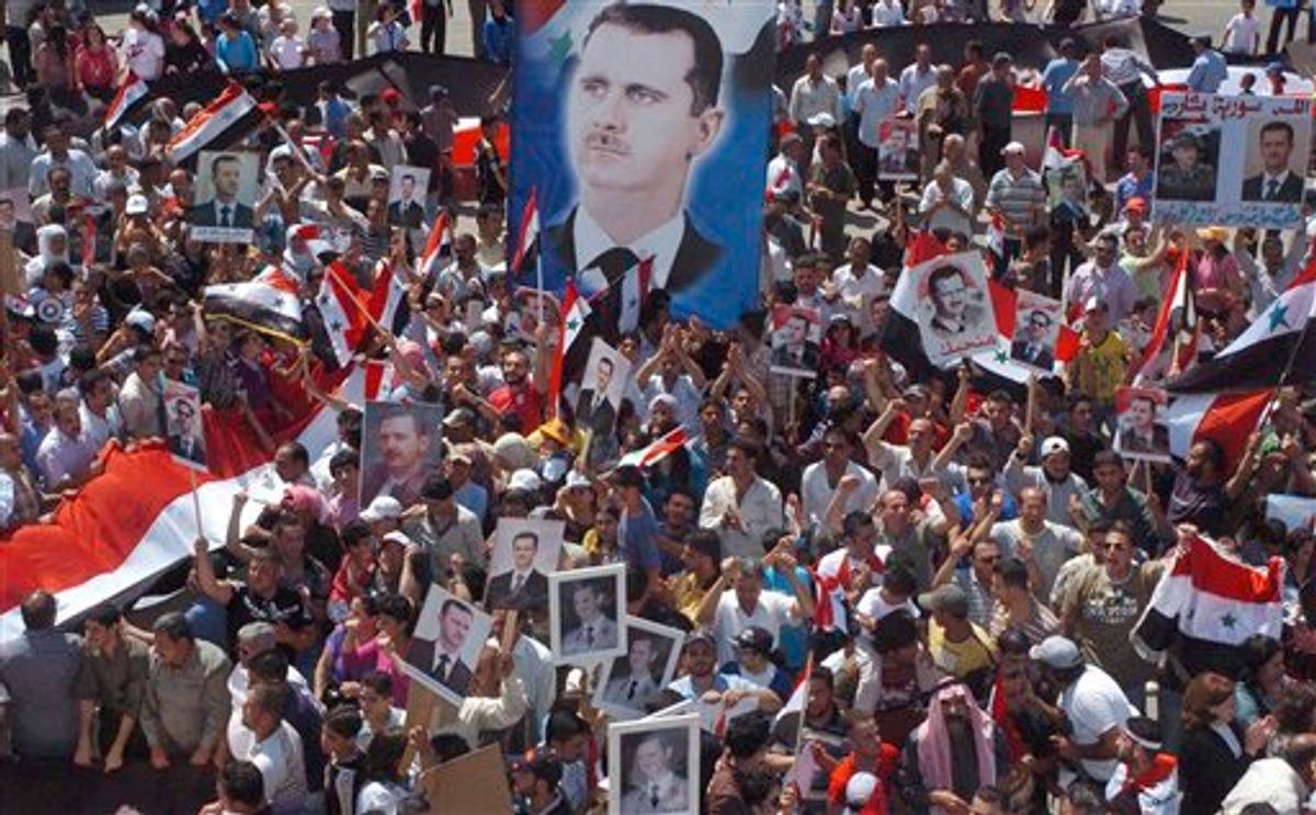 In this photo released by the Syrian official news agency SANA and according to them, Pro-Syrian President Bashar Assad demonstrators, display posters with his image,  during a gathering to show their support, at Ezraa village in Daraa province, Syria, on Wednesday July 6, 2011. Syrian security forces may have committed crimes against humanity during a deadly siege of a western town in May, Amnesty International said Wednesday, citing witness accounts of deaths in custody, torture and arbitrary detention. (AP Photo/SANA) EDITORIAL USE ONLY (AP)