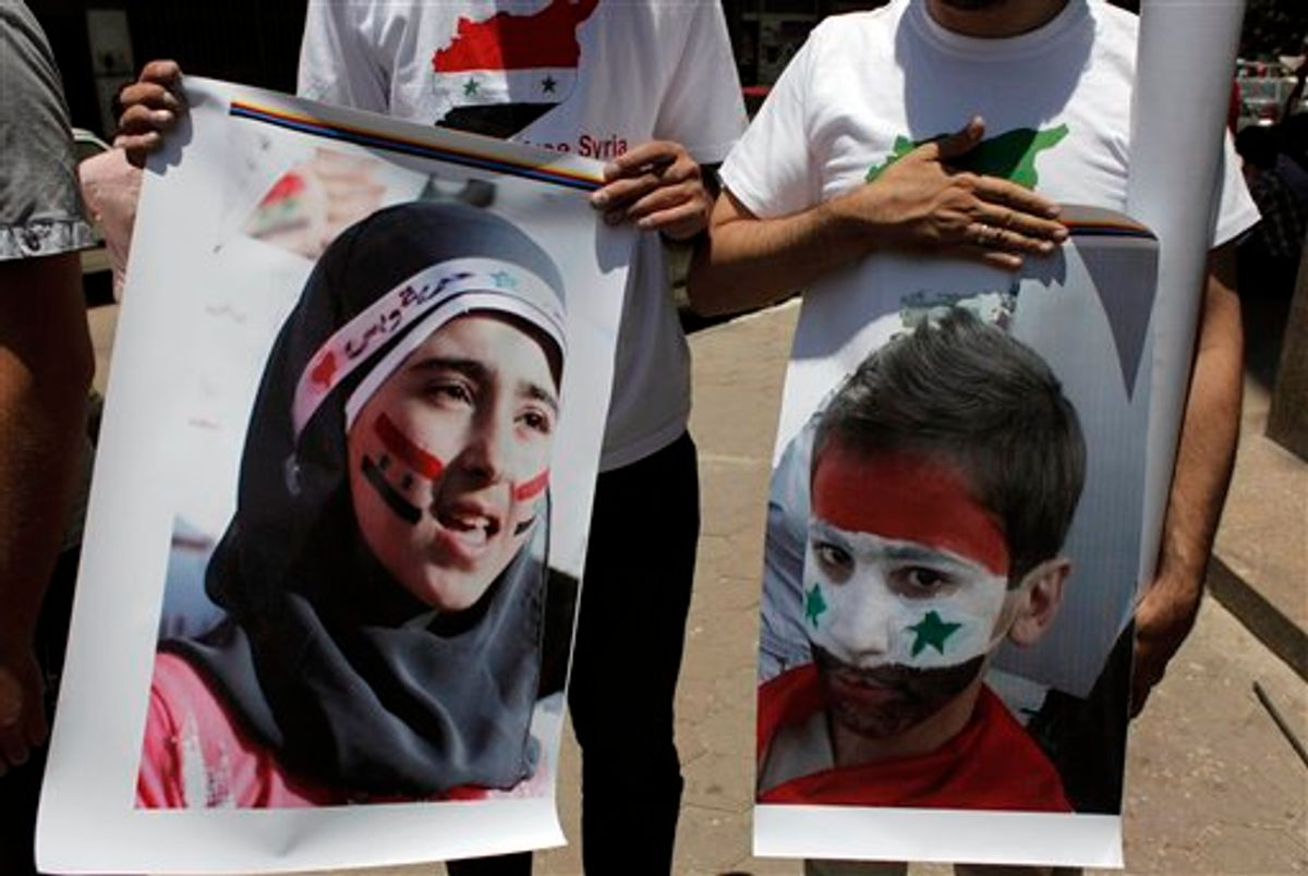 Two protesters carry posters with pictures of unidentified relatives in Syria,  with the Syrian flag colors painted on their faces during an anti-Syrian regime rally near the Syrian embassy in Cairo, Egypt Tuesday, July 5, 2011. Syrian troops fired Tuesday on residents who set up makeshift roadblocks to prevent the advance of tanks ringing the city of Hama, which has become a flashpoint of the uprising against autocratic President Bashar Assad, activists said. (AP Photo/Nasser Nasser) (AP)