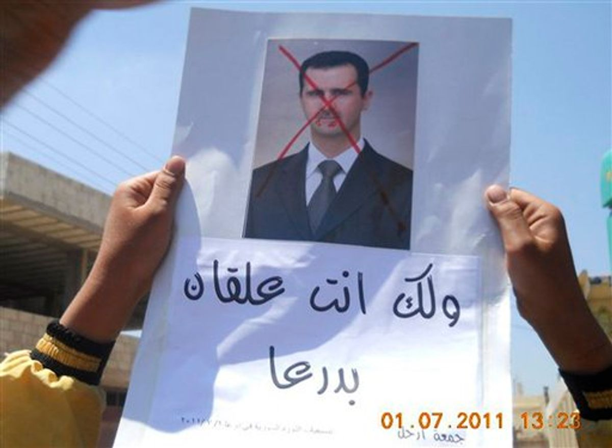 """In this citizen journalism image made on a mobile phone and provided by Shaam News Network, anti-Syrian President Bashar Assad protester, holds up an Arabic placard read:""""You are stuck in Daraa,"""" during a demonstration against the Syrian regime, at Tafas village in Daraa province, southern Damascus, Syria, on Friday July 1, 2011. Hundreds of thousands of protesters flooded cities around Syria on Friday in one of the largest outpourings against the regime of President Bashar Assad since the uprisings began more than three months ago. At least six people were killed in various clashes, activists said. (AP Photo/Shaam News Network) EDITORIAL USE ONLY, NO SALES, THE ASSOCIATED PRESS IS UNABLE TO INDEPENDENTLY VERIFY THE AUTHENTICITY, CONTENT, LOCATION OR DATE OF THIS HANDOUT PHOTO (AP)"""