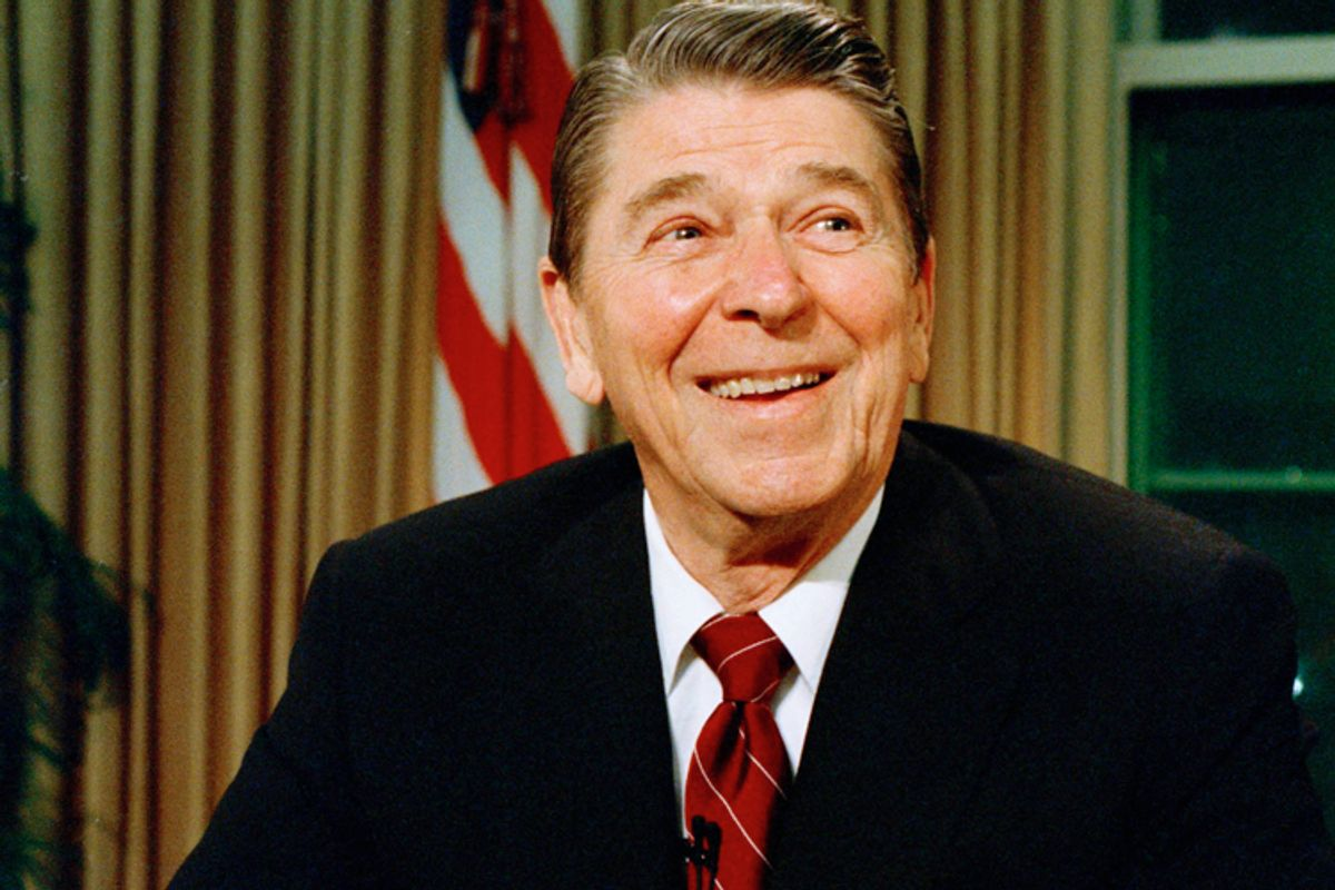 President Ronald Reagan smiles as he poses for photographers after delivering a speech on television, in this Dec. 11, 1987 file photo.