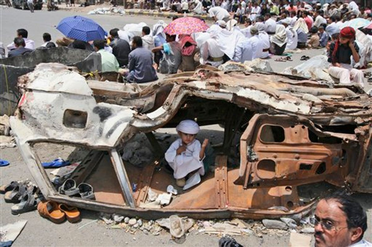 A Yemeni boy sits inside a wreckage of a car while anti-government protestors, attend Friday prayers, during a demonstration demanding the resignation of Yemeni President Ali Abduallah Saleh, in Taiz, Yemen, Friday, July 15, 2011. Tribesmen killed a Yemeni army officer and two of his aides in an ambush Friday, and government shelling killed two civilians in a volatile southern area, officials said. (AP Photo/Anees Mahyoub) (AP)