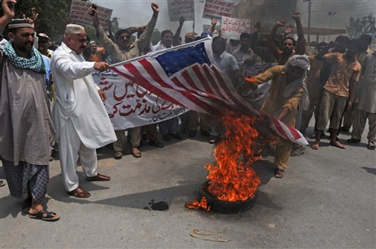 Pakistani protesters burn a representation of an American flag during a rally to condemn U. S. drone attacks targeting al-Qaida and Taliban militants' hideout in Pakistani tribal belt of Waziristan along the Afghanistan border, on Thursday, July 7, 2011 in Mutan, Pakistan. (AP Photo/Khalid Tanveer) (AP)