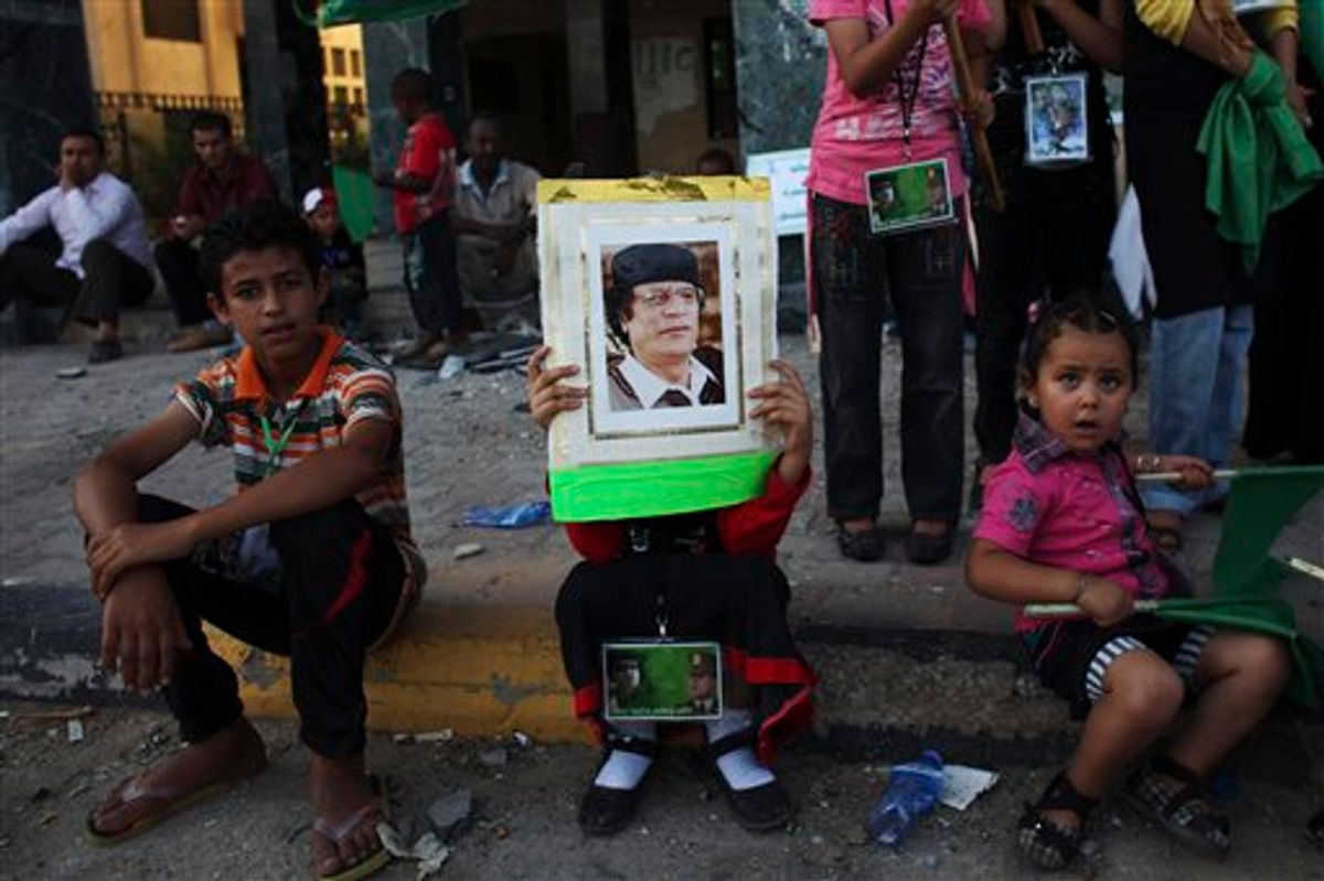 In this photo taken on a government-organized tour, a child rests as she holds up a picture of LIbyan leader Moammar Gadhafi during a rally in the town of Zawiya, roughly 50 km (30 miles) west of Tripoli, Libya, Saturday, July 16, 2011. Ten rebel fighters were killed in an advance on the strategic oil town of Brega in eastern Libya on Saturday, with rebel forces sweeping the outskirts for land mines so they could move in, officials said. The advance came after Libya's main opposition group was recognized by more than 30 nations, including the U.S., as Libya's legitimate government. Friday's decision potentially frees up billions of dollars in cash that the rebels urgently need. (AP Photo/Tara Todras-Whitehill) (AP)