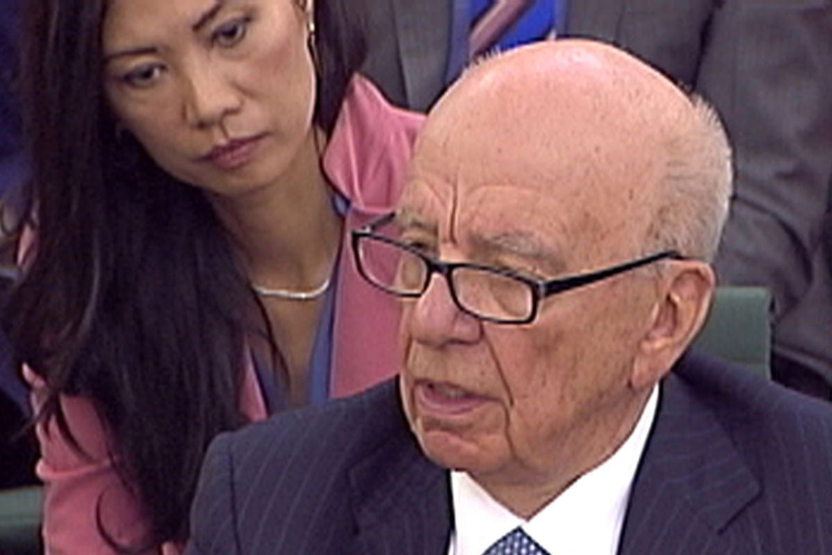 Wendi Deng ( L) watches as her husband, News Corp Chief Executive and Chairman Rupert Murdoch, is questioned during a parliamentary committee hearing on phone hacking at Portcullis House in London July 19, 2011.  Later, Murdoch was attacked by a protester on Tuesday while giving evidence to a British parliamentary committee at which he defended his son and his company over a scandal that has rocked the British establishment. REUTERS/Parbul TV via Reuters Tv (BRITAIN - Tags: CRIME LAW MEDIA BUSINESS) FOR EDITORIAL USE ONLY. NOT FOR SALE FOR MARKETING OR ADVERTISING CAMPAIGNS       (© Reuters Tv / Reuters)