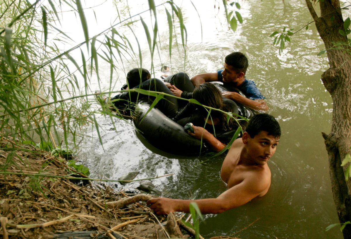 A group of illegal aliens wait on the U.S. side of the Rio Grande river, after floating across in a tire tube, in Laredo, Texas May 2, 2006. U.S. Border Patrol agents intercepted the group and they eventually went back to Mexico.   REUTERS/Rick Wilking (Reuters)