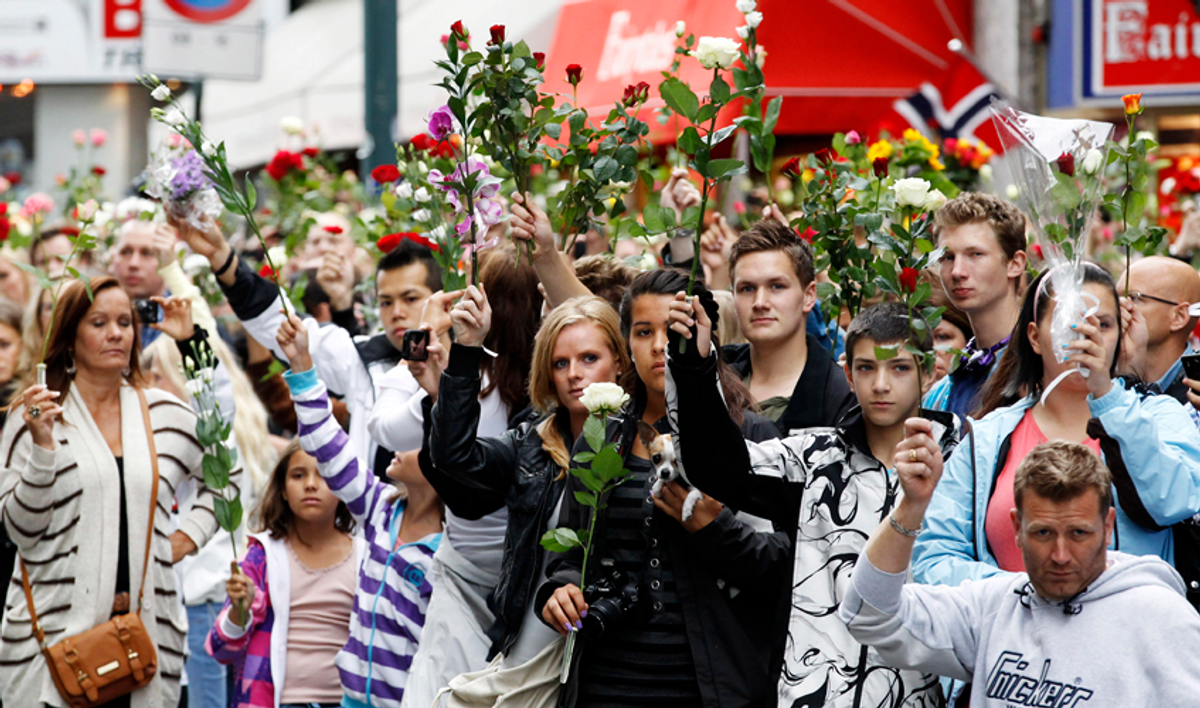 People hold up flowers as they take part in a memorial march for the victims of the killing spree and bomb blast in downtown Oslo