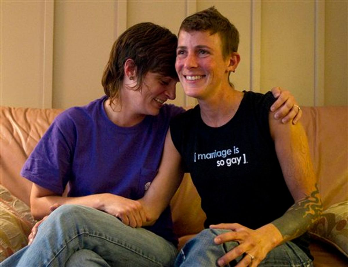 In a July 25, 2011 photo, lesbian couple Jennifer Tipton, left, and Olivier Odom are seen at a coffee house in Knoxville, Tenn. The couple are calling for Dollywood Splash County to be more inclusive to its guests after they were asked to reverse the pro-gay marriage T-shirt worn by Odom, during a recent visit.  (AP Photo/Knoxville News Sentinel, Saul Young)  (AP)