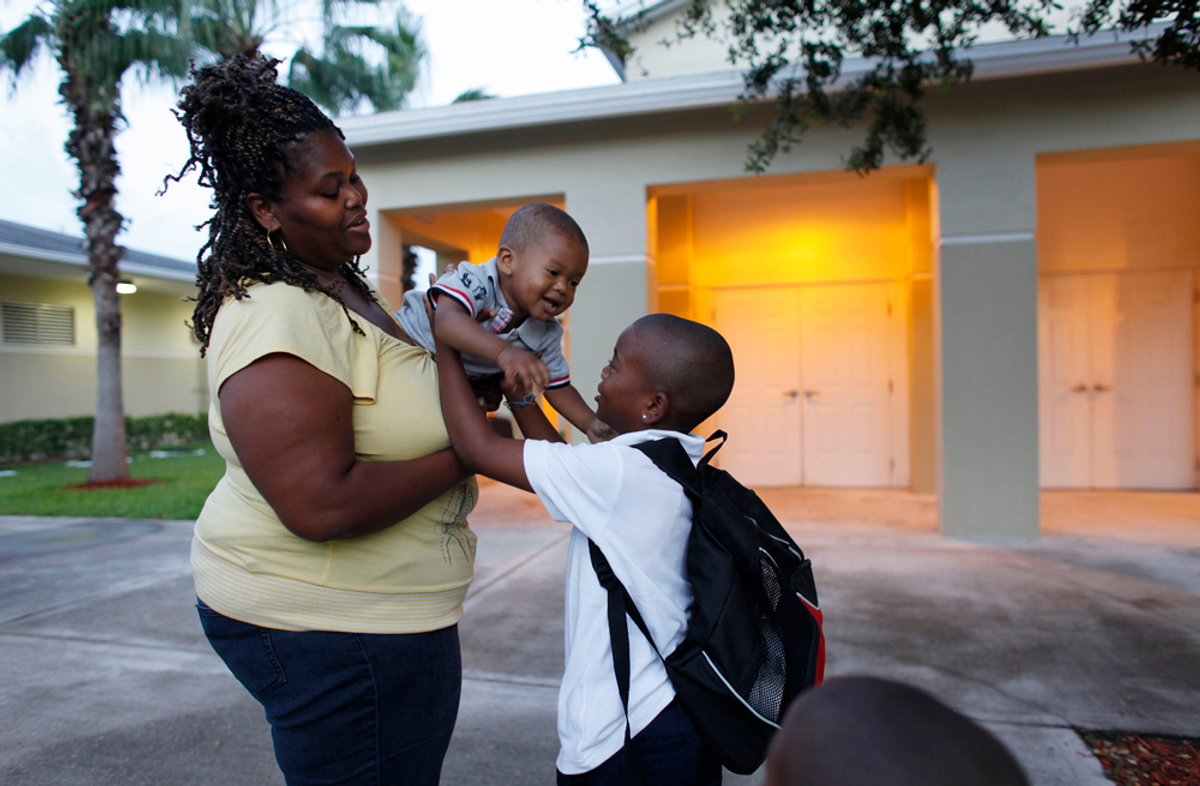 Elias Pirela, 6, right, holds his brother Ahmad Phillips, center, as he stands with his mother Latasha Phillips, 33, left, before leaving for the first day of school from his temporary home at the Community Partnership for Homeless in Miami, Monday, Aug. 23, 2010