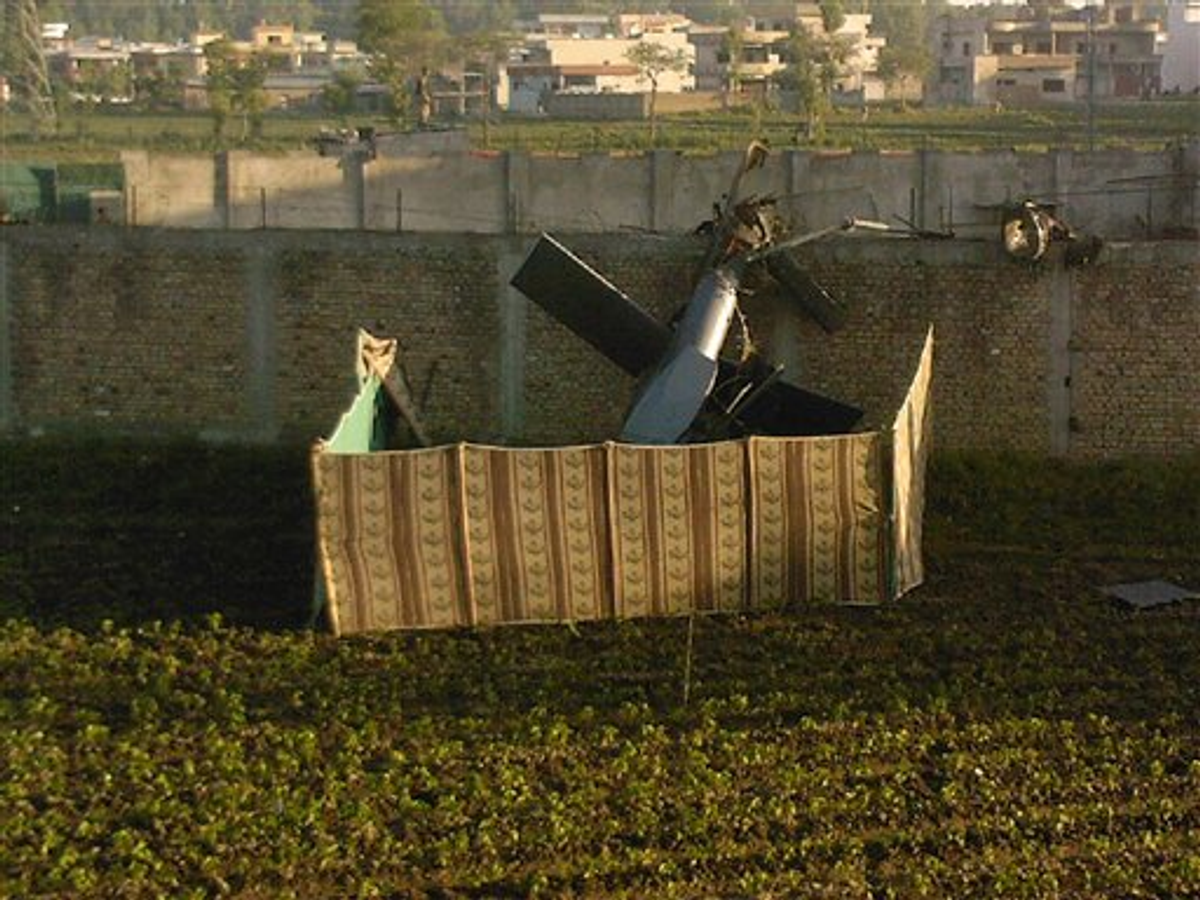 A photo taken by a local resident shows the wreckage of a helicopter next to the wall of the compound where Osama bin Laden was shot and killed in Abbottabad, Pakistan on Monday, May 2, 2011