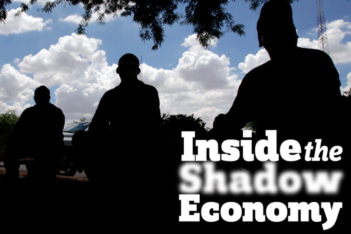 Day laborers sit in a parking lot in Phoenix.  (AP/Matt York)