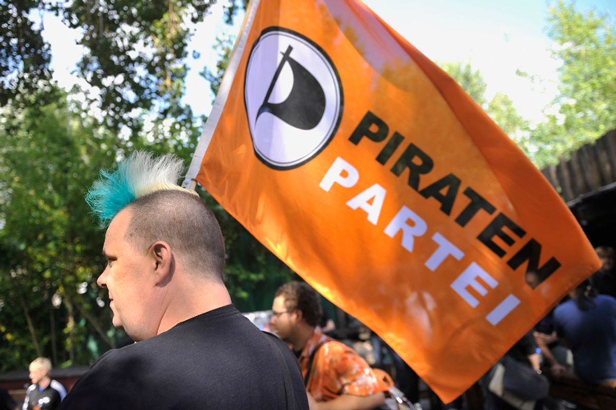 A member of Germany's Pirate Party holds a flag of the party  (AP/Gero Breloer)