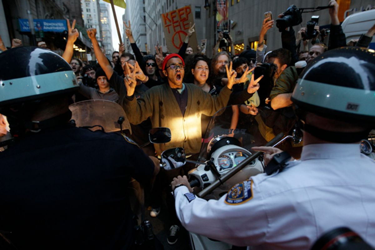 Demonstrator affiliated with the Occupy Wall Street protests confront New York City police officers as they march on the street in the Wall St. area, Friday, Oct. 14, 2011 in New York.  (AP/Mary Altaffer)