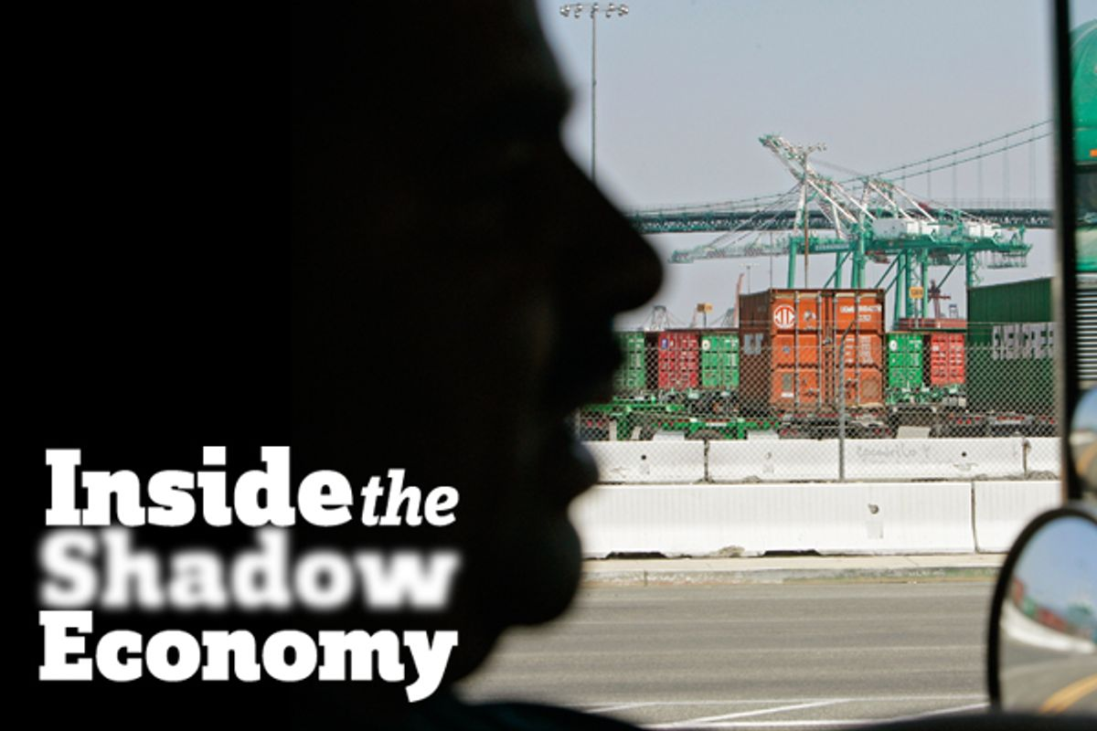 A truck driver is silhouetted as he drives his truck to the port of Long Beach, Calif.   (AP/Ric Francis)