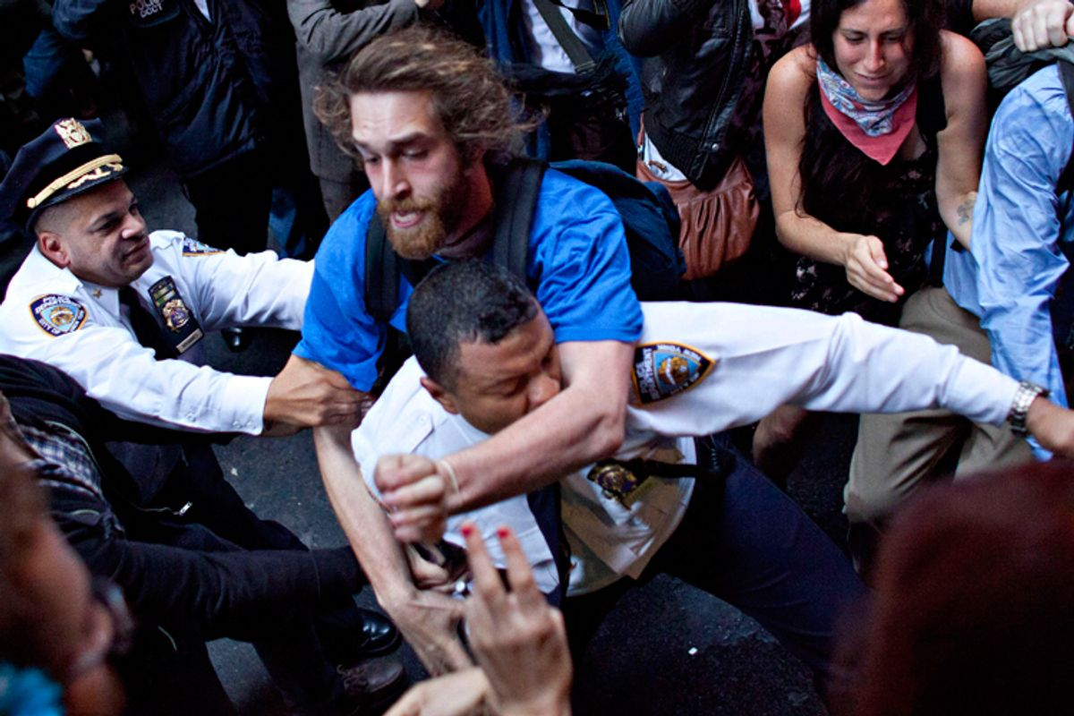 A man affiliated with the Occupy Wall Street protests tackles a police officer during a march towards Wall Street in New York, on Friday.  The Washington Post published this photo on its front page Saturday. (AP/Andrew Burton)