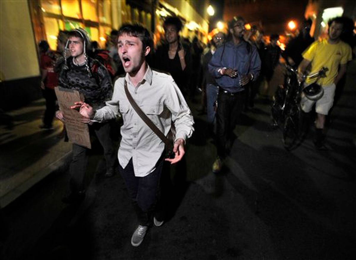 """Demonstrators with """"Occupy Boston"""" march toward  the police station where fellow demonstrators were brought after police arrested people sleeping in an expansion of the Occupy Boston tent village in Boston, in the early morning hours of Tuesday, Oct. 11, 2011.    (AP/Josh Reynolds)"""