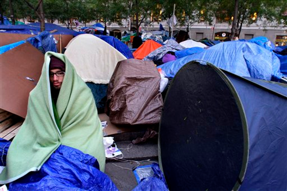 A protester is wrapped in a blanket to stay warm at the Occupy Wall Street protest at Zuccotti Park on Friday, Oct. 28, 2011 (AP Photo/Bebeto Matthews)