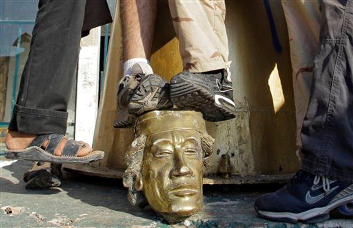 Rebel fighters trample on a head of Moammar Gadhafi inside the main compound in Bab al-Aziziya in Tripoli, Libya, this past August.    (AP/Sergey Ponomarev)