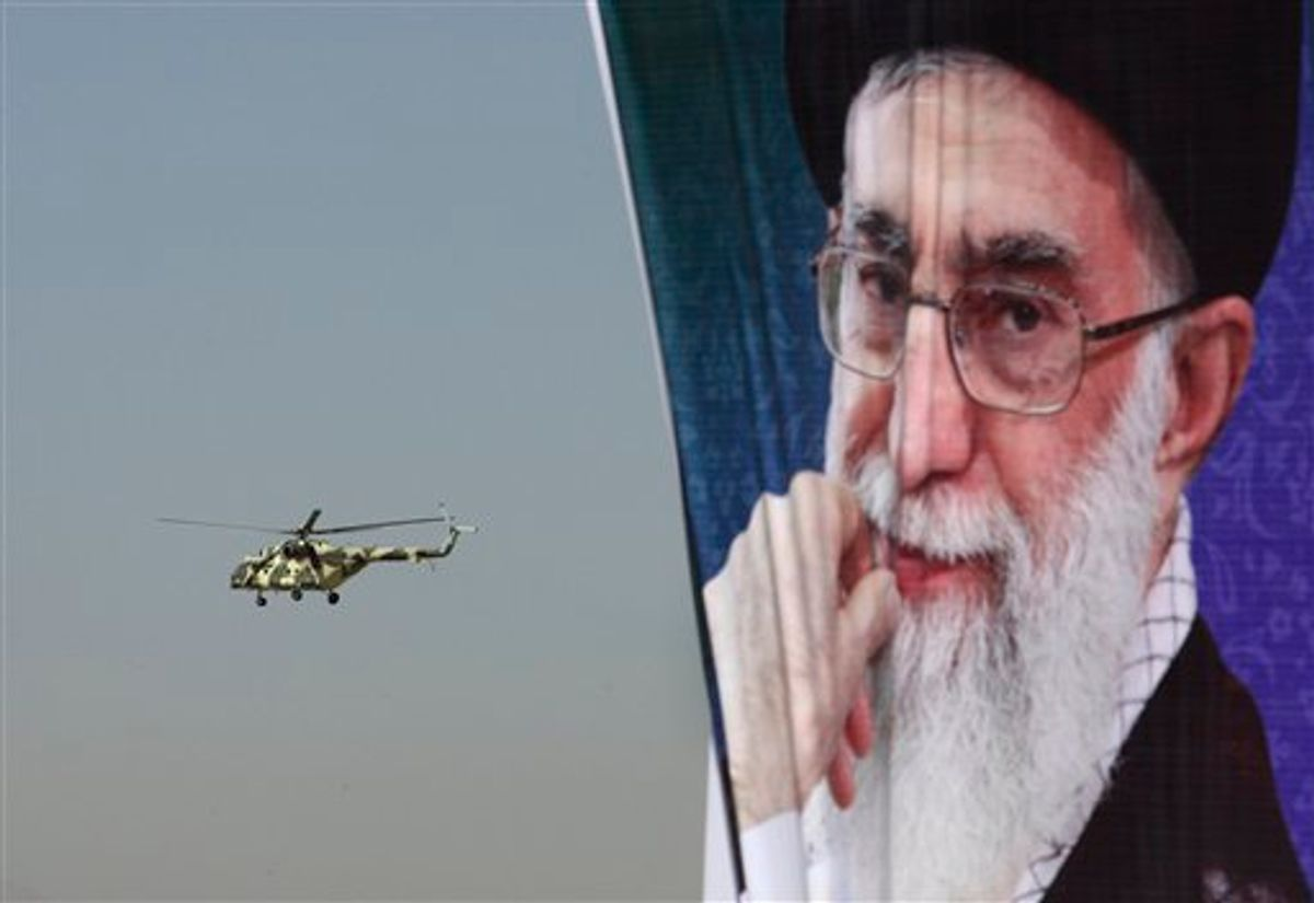"""A police helicopter flies behind a poster of Iranian supreme leader Ayatollah Ali Khamenei during an exercise commemorating """"Police Week"""", in downtown Tehran, Iran, Friday, Oct. 7, 2011.  (AP Photo/Vahid Salemi)"""