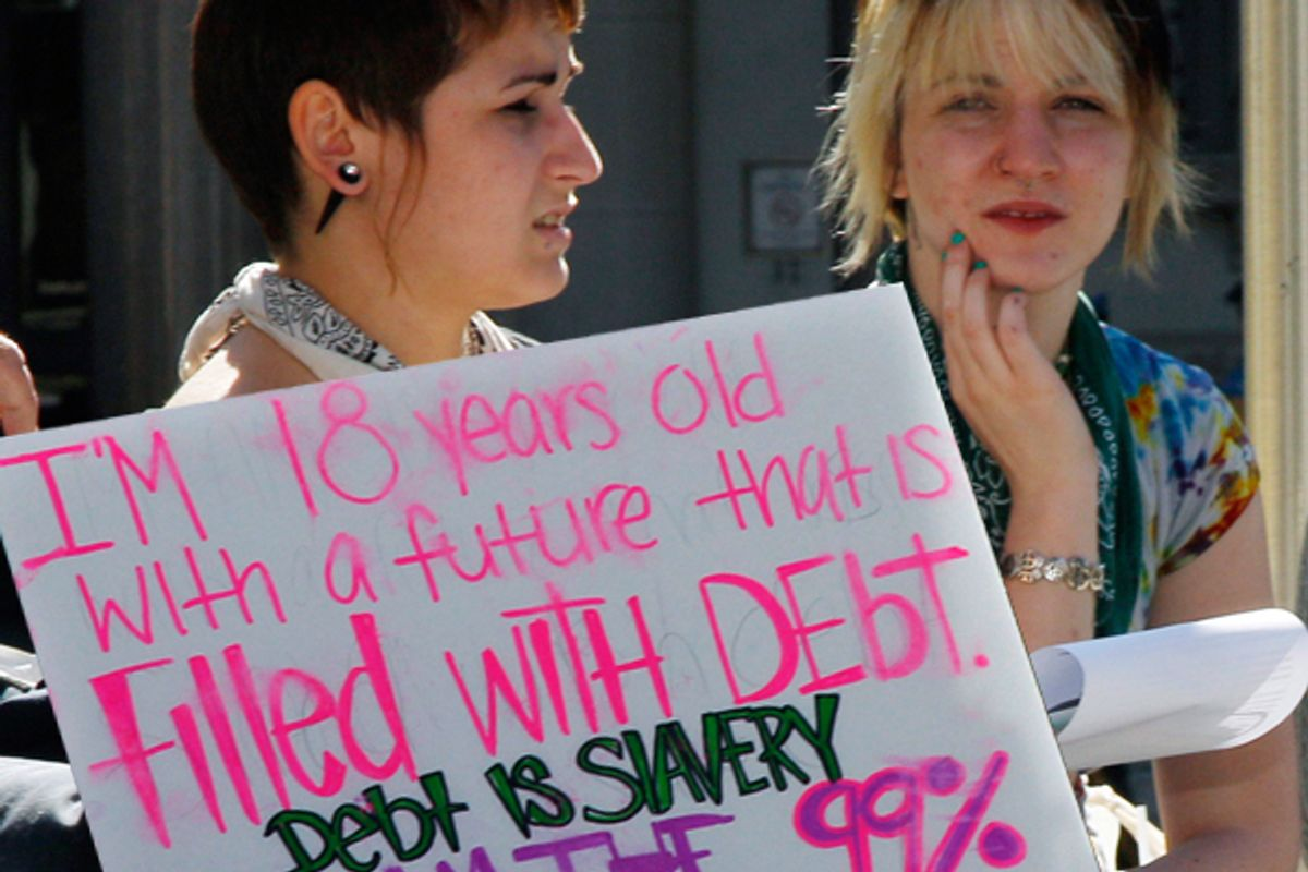 """Two young women sit next to a sign as they listen to a speakers during a protest gathering across from the Statehouse in Trenton, N.J., Thursday, Oct. 6, 2011, as the """"Occupy Wall Street"""" movement in New York has spread across the Hudson River."""