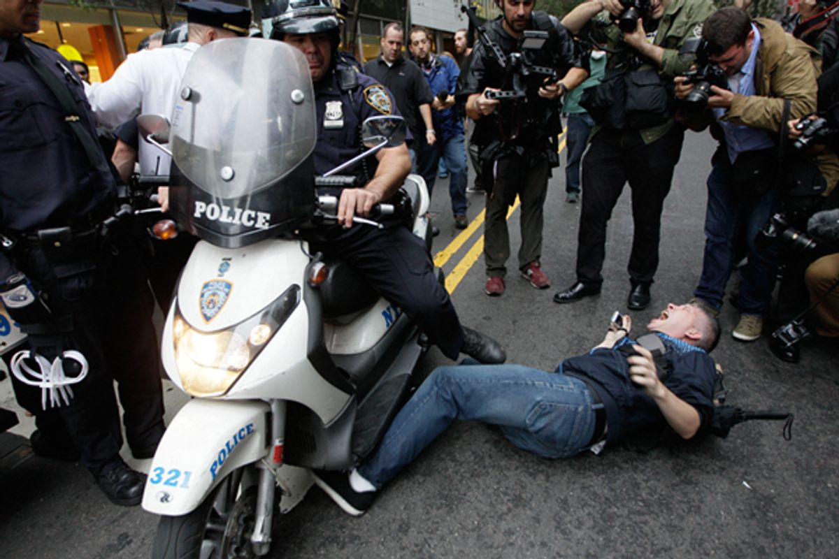 A New York City police officer runs over a National Lawyers Guild observer as Occupy Wall Street demonstrators march through the streets near Wall Street, Friday, Oct. 14, 2011, in New York.      (AP/Mary Altaffer)