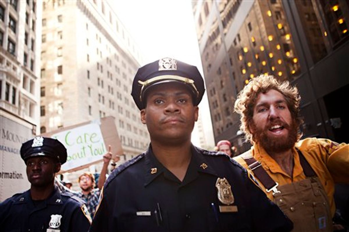 """Two New York City police officers walk alongside a protestor affiliated with the """"Occupy Wall Street"""" protests outside Zuccotti Park after the arrest of two men in New York, on Monday, Oct. 10, 2011. (AP/Andrew Burton)"""