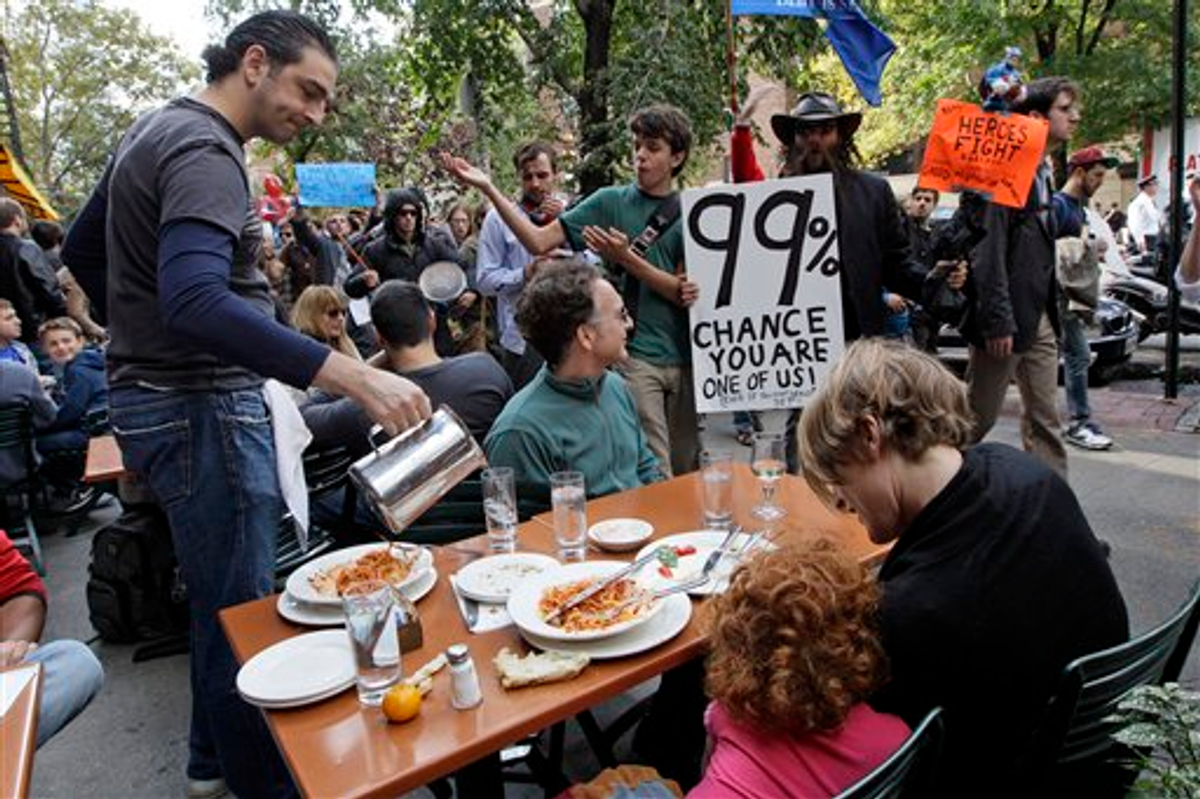 Demonstrators affiliated with the Occupy Wall Street march past a family dining at an outdoor restaurant, Saturday, Oct. 15, 2011 in New York    (AP Photo/Mary Altaffer)