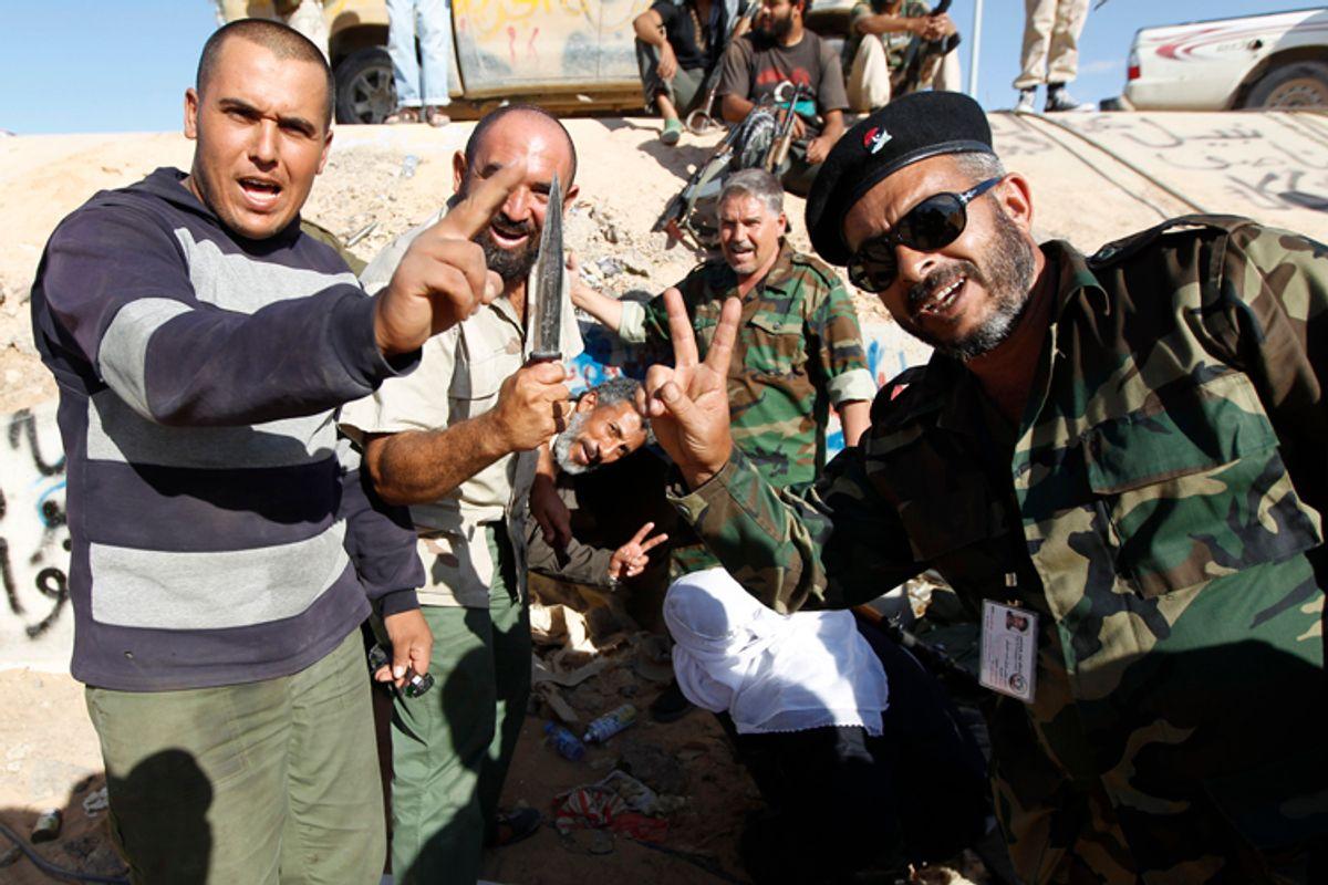 Anti-Gaddafi fighters celebrate at the drain where Muammar Gaddafi was hiding before he was captured in Sirte October 20, 2011.      (Thaier Al-sudani / Reuters)