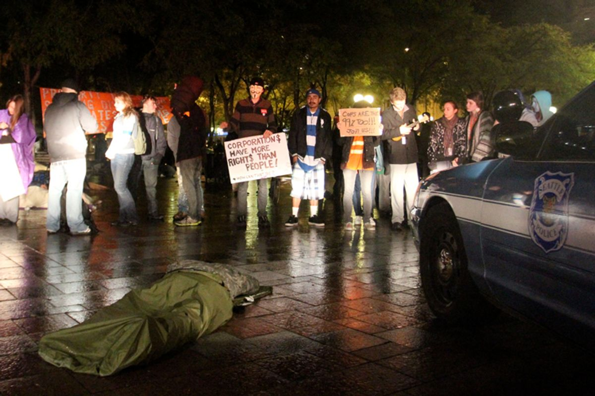 Several Occupy Seattle protesters stand in front of Seattle Police patrol cars in Westlake Park in downtown Seattle early Tuesday Oct. 11, 2011. (AP/Manuel Valdes)