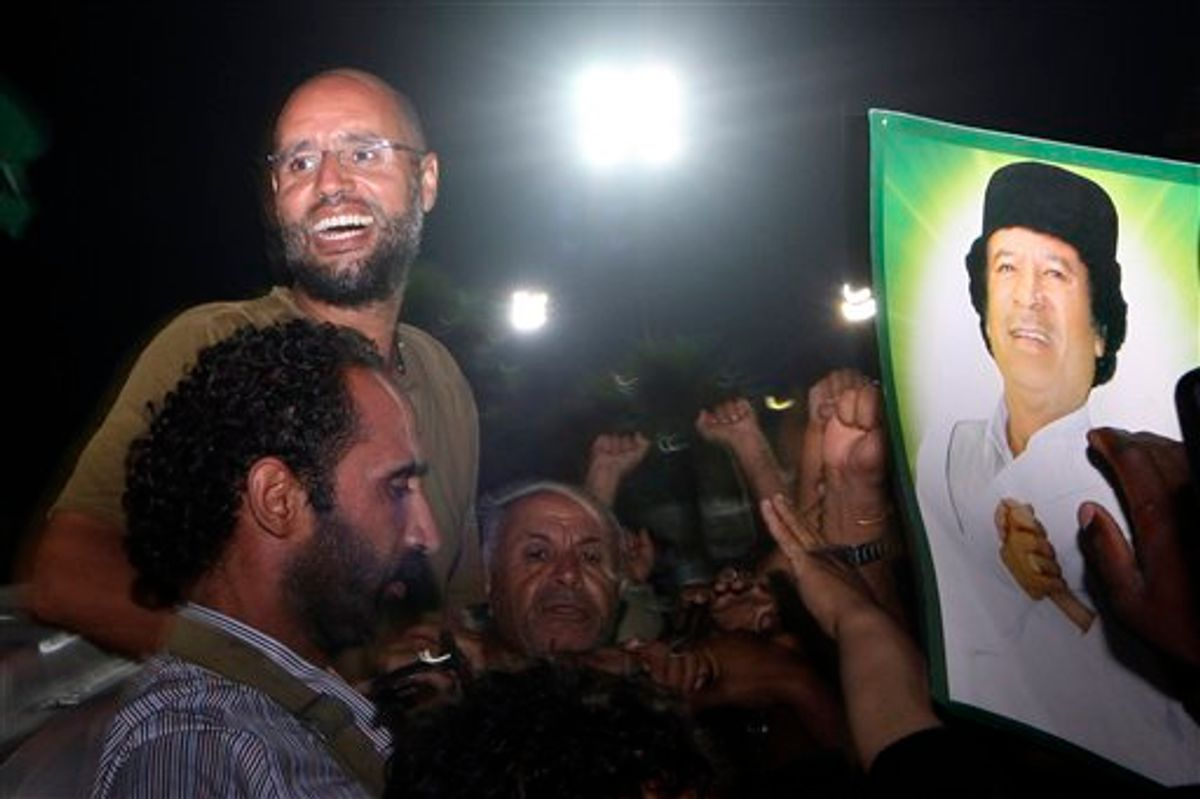 File - Moammar Gadhafi's son, Seif al-Islam, top left, gestures to troops loyal to his father in Tripoli, Libya, Tuesday, Aug. 23, 2011.  (AP/Imed Lamloum)