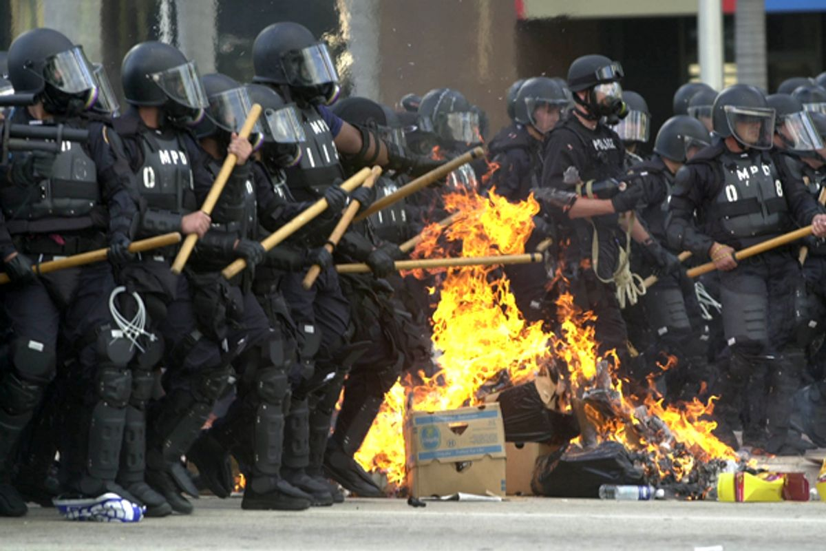 Miami riot police march through burning trash during a free trade protest in November 2003.   (AP)
