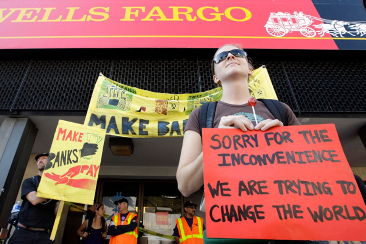 Occupy Oakland protesters stand outside of a Wells Fargo bank in Oakland, Calif., Weds., Nov. 2, 2011.      (AP/Paul Sakuma)
