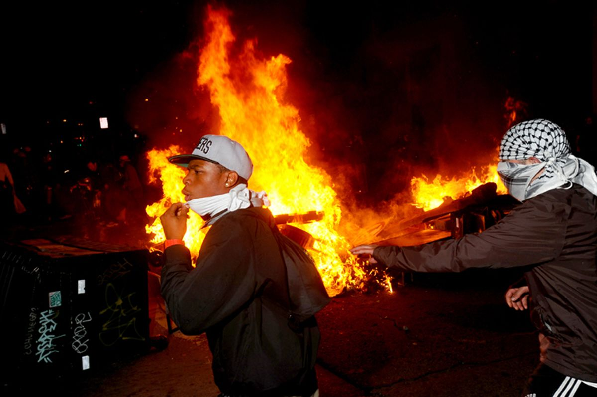 Occupy Oakland protesters pass a burning garbage heap during a confrontation with police on Thursday, Nov. 3, 2011, in Oakland, Calif.       (AP/Noah Berger)