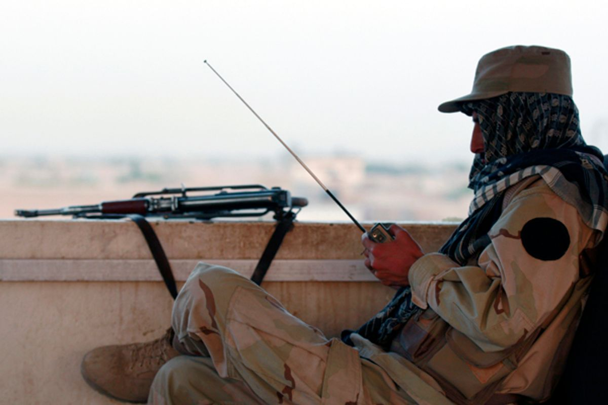A private security organization contractor listens to a radio during his duty at guard tower in Camp Nathan Smith in Kandahar City       (Nikola Solic / Reuters)